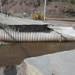Washed out road with underground pipelines exposed