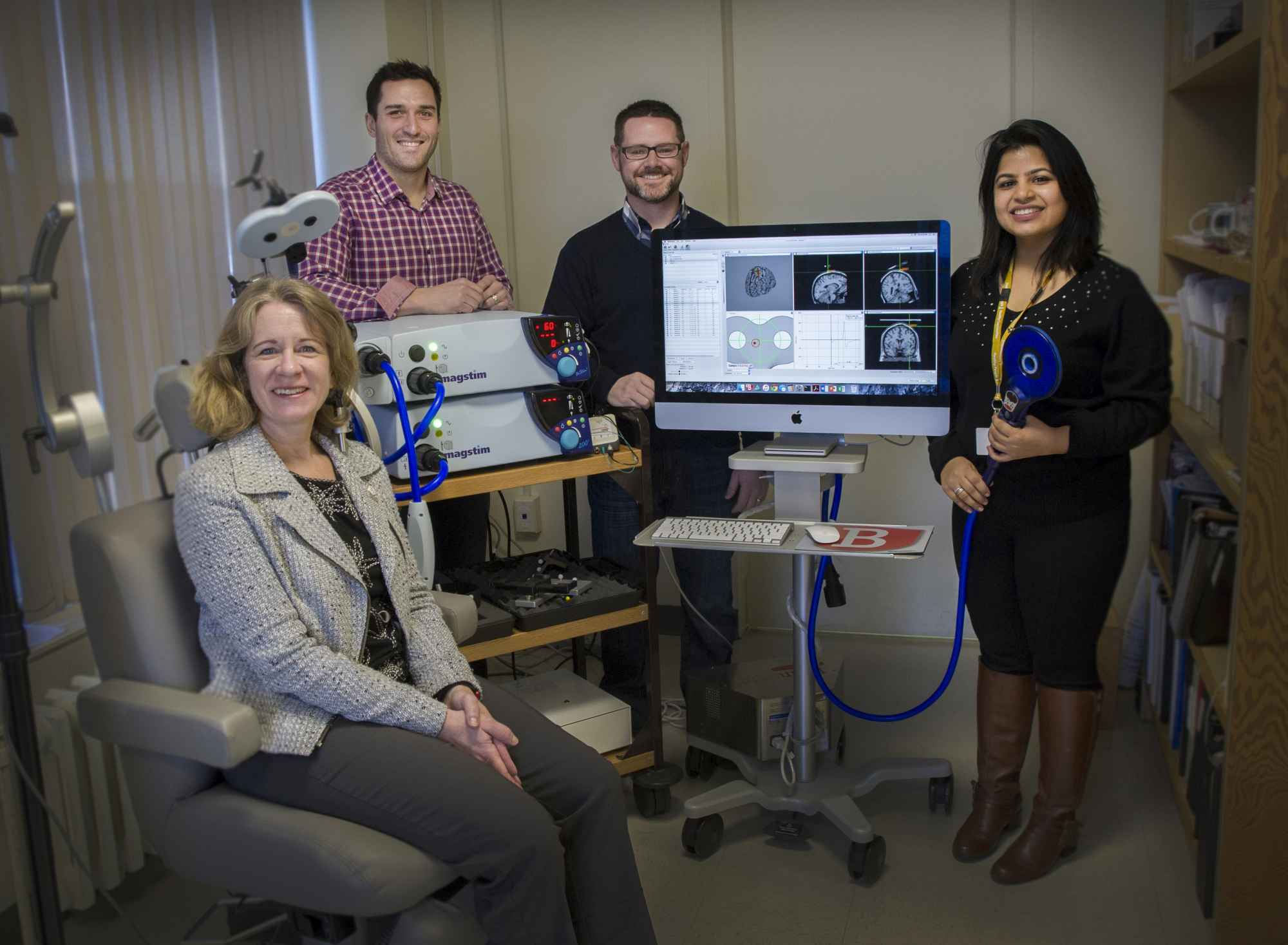 Drs. Michelle Ploughman, Duane Button, and Kevin Power along with Geetika Grover stand with equipment used during testing.