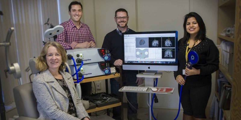 Drs. Michelle Ploughman, Duane Button, and Kevin Power along with Geetika Grover stand with equipment used during testing