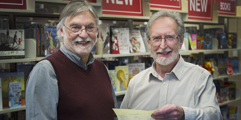 Professorts Fred Hawksley and Alex Hickey stand in the resource centre library in the Education building and look at the field notebook they created for the Great War Project.
