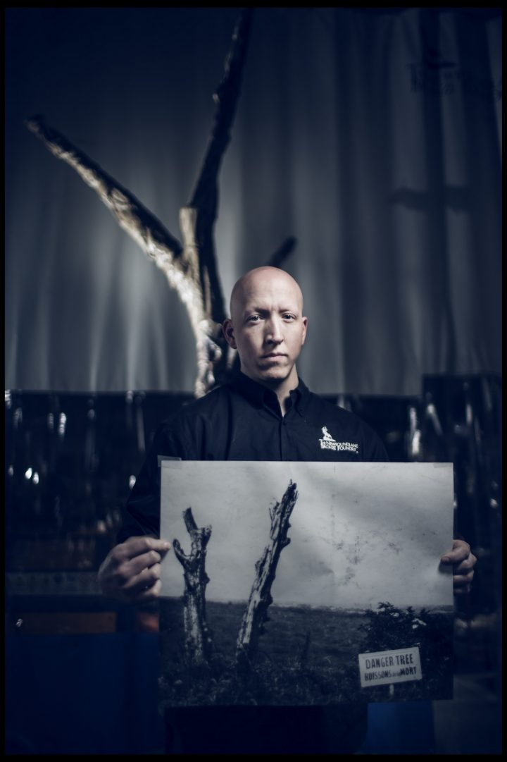 Sculptor Morgan MacDonald holds an archival photo of the Danger Tree in Beaumont-Hamel in front of his Danger Tree sculpture.