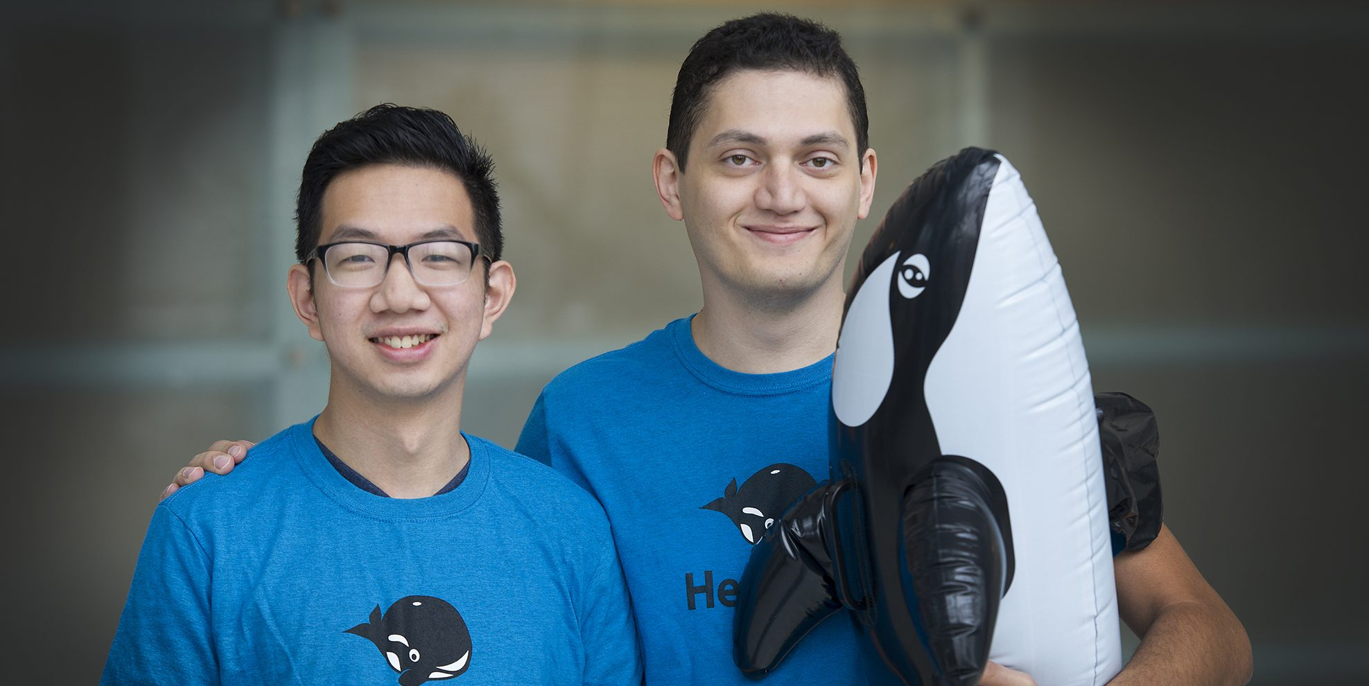 "Joe Teo and Sahand Seifi of HeyOrca! hold their mascot. They pass around the inflatable whale in meetings to indicate who has the floor. The whale is their ""conche"" of sorts."