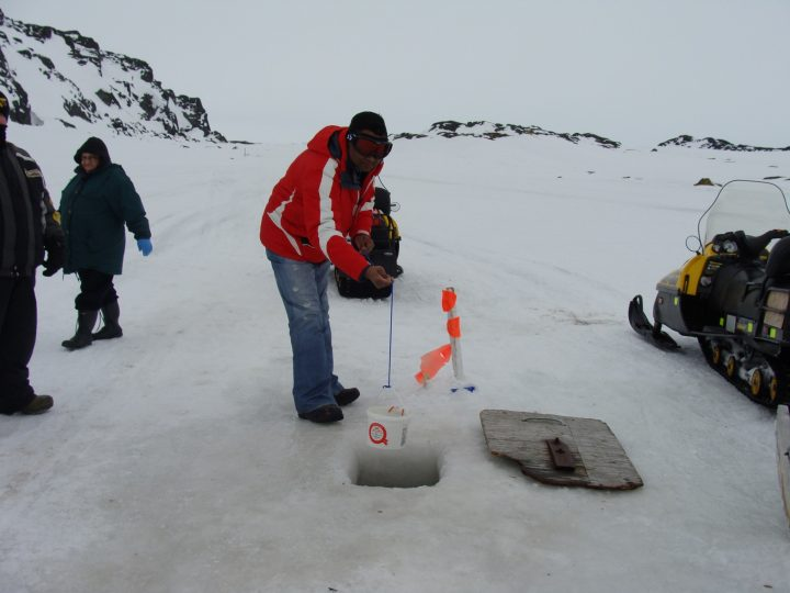 Dr. Atanu Sarkar tests the quality of water under the ice in Black Tickle, Labrador.