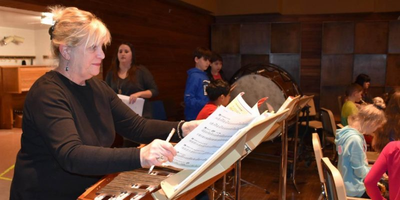 Ms. Korna Brophy arranges music on stage at the Cook Recital Hall