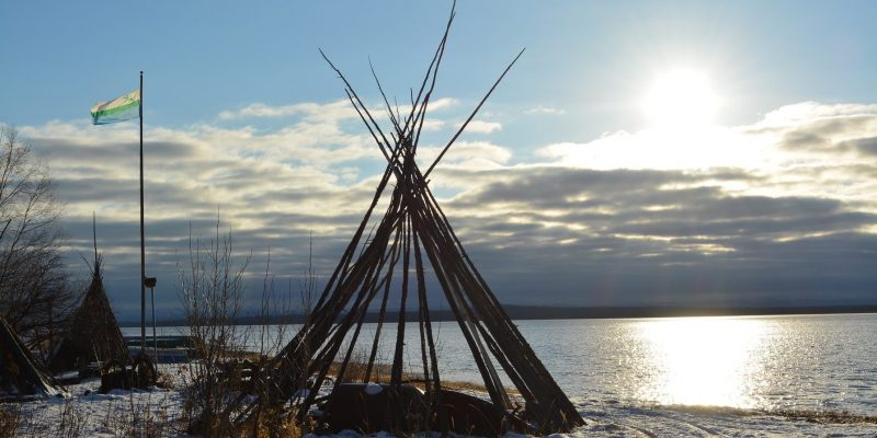A teepee frame in the sunset on the edge of a lake