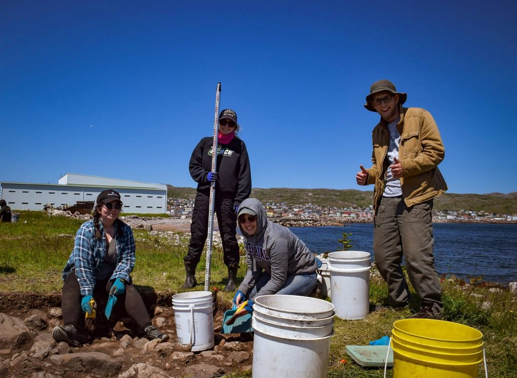 From left to right: Nancy Butler, Rachael Green, Meghann Livingston and Benjamin Feaver excavate Anse a Betrand, the old airport building can be seen in the background.
