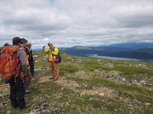 Dr. Stephen Piercey (yellow jacket) talks to colleagues about the geology around the Kudz Ze Kayah VMS deposits, Finlayson Lake region, Yukon, summer 2017