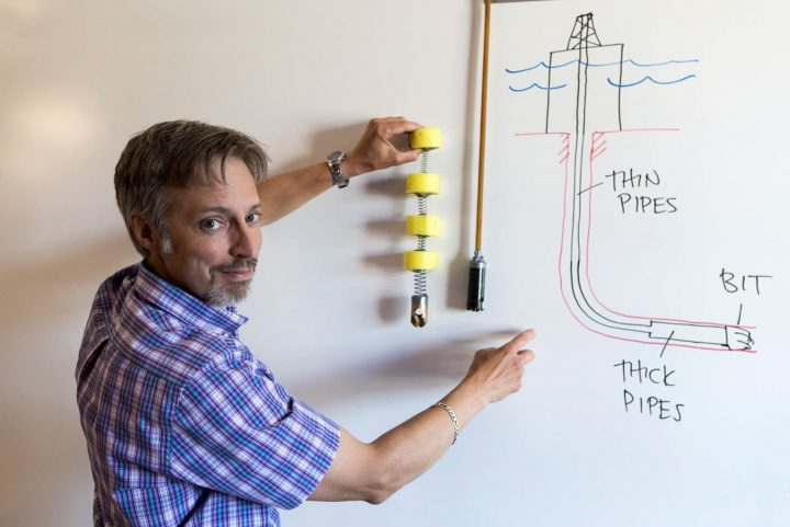 Dr. Geoff Rideout illustrates vibrations in a drill string by stretching a piece of surgical tubing with a tiny drill bit on the end. Next to him is a mock-up of a mass-spring-mass-spring lumped segment model, also with a tiny drill bit on the end.