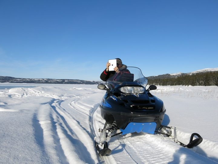 Man on snowmobile on the ice holding an iPad