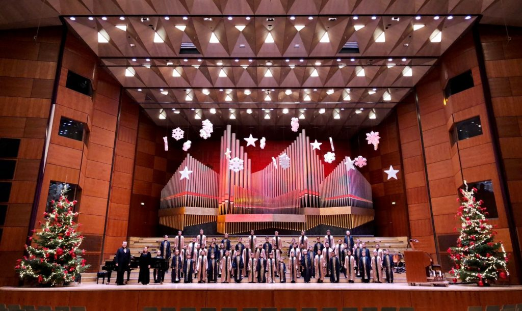 Boys dressed in choir gowns on a large stage with Christmas trees on either end.