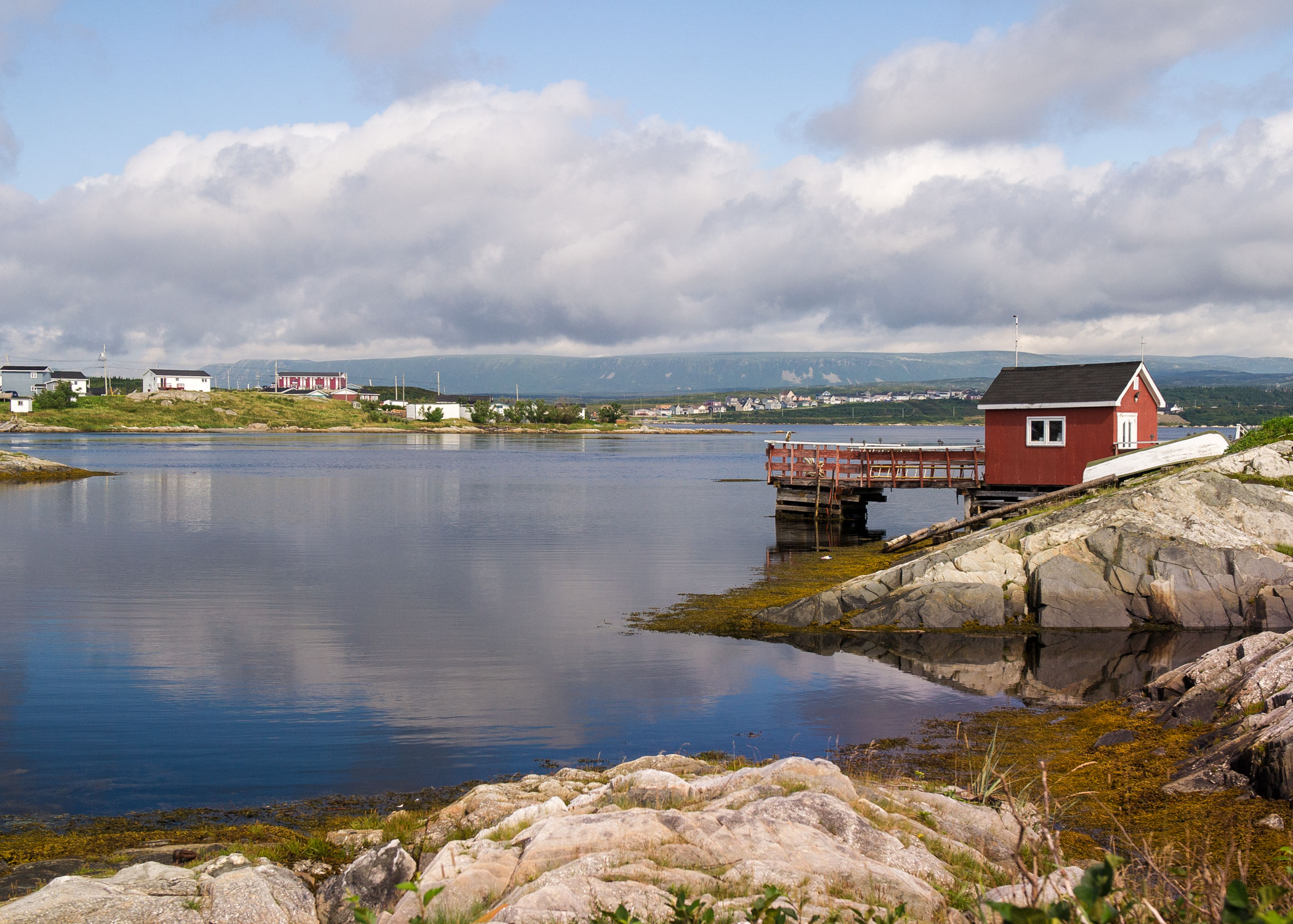 A landscape photo showing a rocky shoreline, houses and a fishing stage