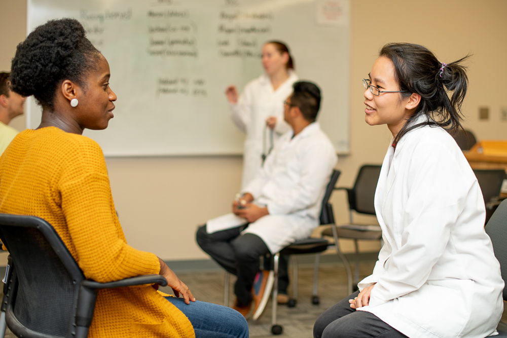 Two Nursing students sit face to face talking to each other in School of Nursing classroom