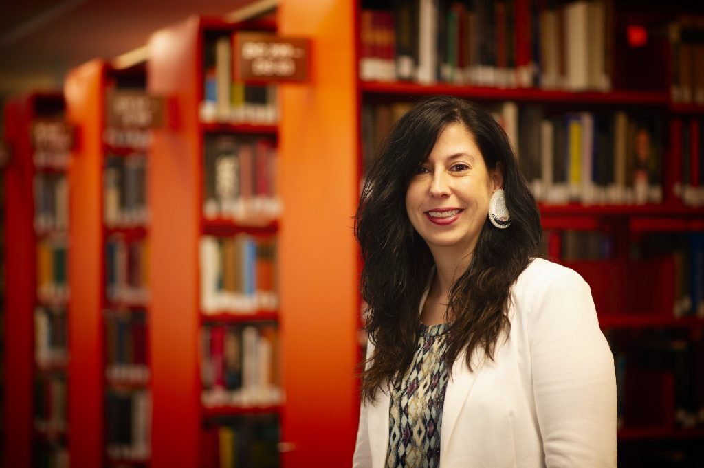 Erica Hurley stands in front of bookcases at the Grenfell campus library.