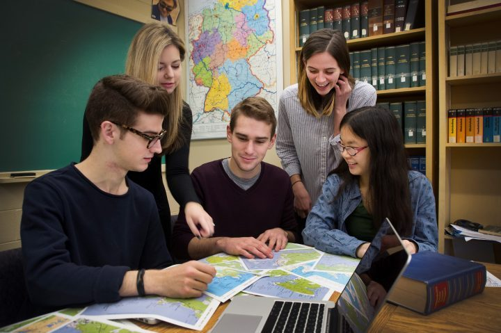 A group of students gather around a table full of maps.