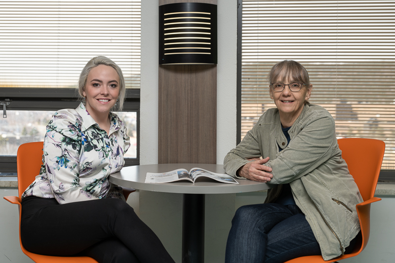 Two women sit in the learning commons with a copy of a magazine article about mental health nursing they co-wrote