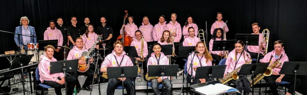 Members of the student jazz ensemble smile together in the CITL production studio.