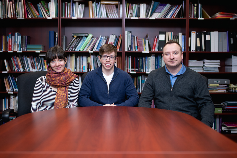 three people sitting at a table in front of a bookshelf looking at the camera